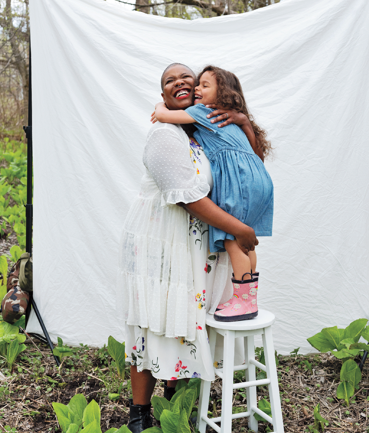 a mother hugs her preschooler, who is standing on a stool