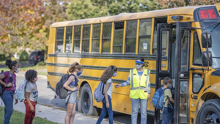 Students getting on the bus wearing protective face coverings due to new COVID-19 regulations.