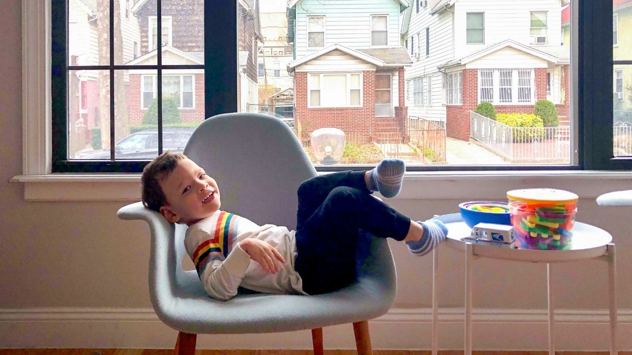 a kid lying in a chair by the window