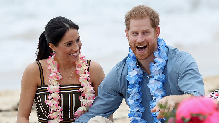 Prince Harry and Meghan Markle laughing on the beach wearing floral garlands
