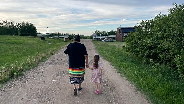 a grandmother and granddaughter walking hand-in-hand