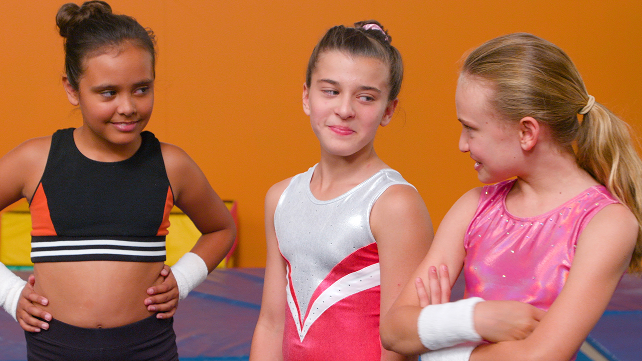 A still from A 2nd Chance Rivals showing three young gymnasts looking tough towards each other