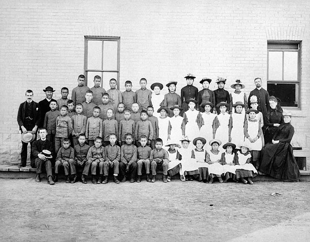 a group of indigenous student and residential school staff posing in front of a school with boys on the left side and girls on the right side