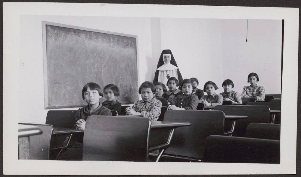 a photo of young female indigenous students in a residential school classroom in 1940