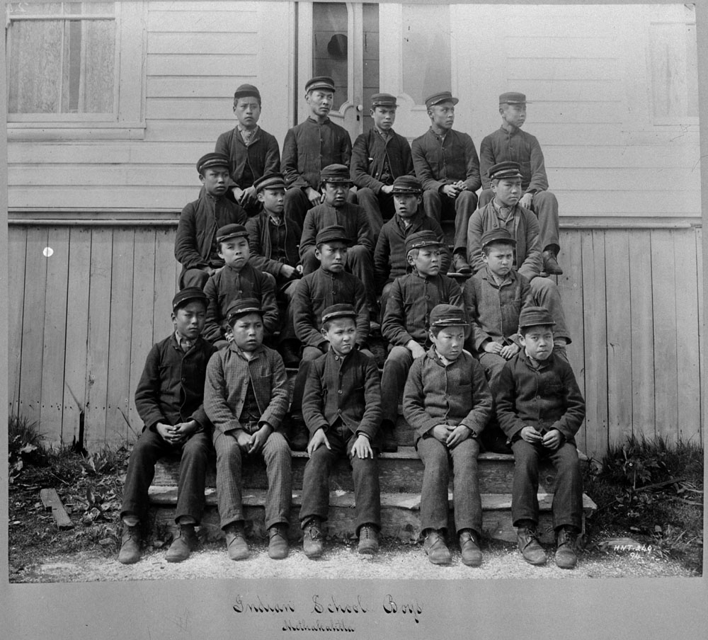 nineteen indigenous students wearing uniforms seated on a series of steps