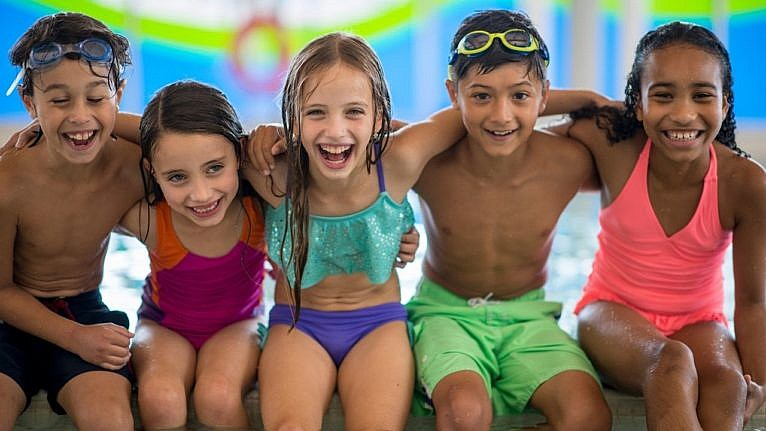 five kids sitting on a pool deck and smiling at the camera