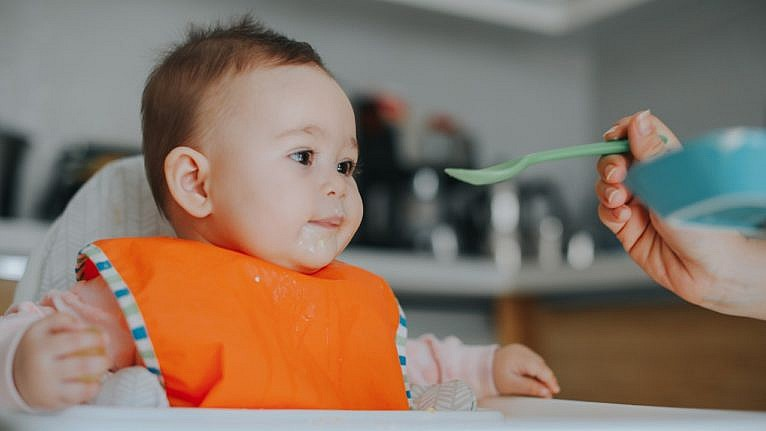 a baby sits in a high chair wearing an orange bib and being fed baby food on a blue spoon