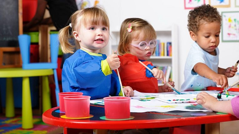 three young children painting at a table in a daycare setting