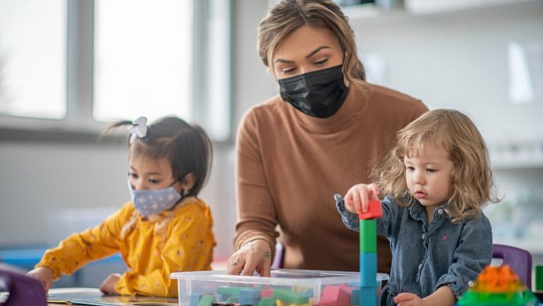 a masked daycare worker playing blocks with two children at a table