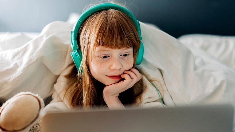 young girl wearing headphones and watching something on her laptop
