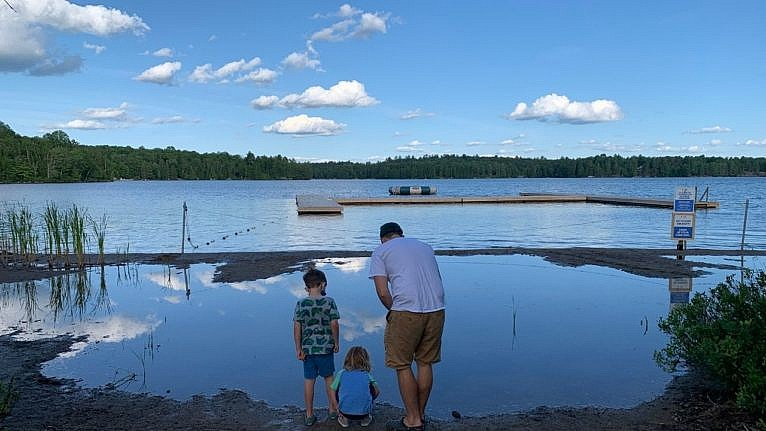 dad and two sons by a lake