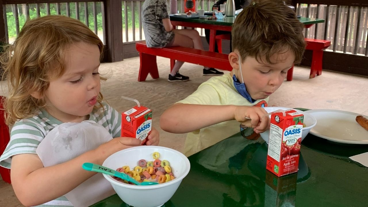 two little boys eating fruit loops and apple juice