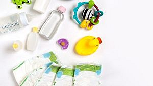 various baby products laid out on a white surface including diapers baby oil and a yellow rubber ducky