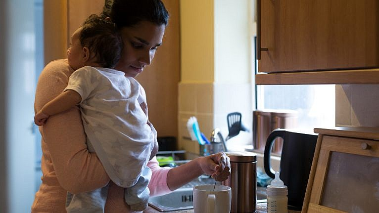 a mom holds her newborn while stirring a cup of coffee in the kitchen
