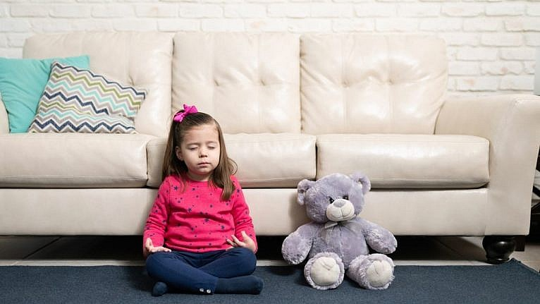 little girl sitting on the floor with her stuffed bear