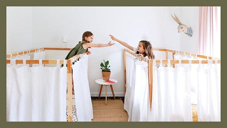 Two girls touch hands from their curtained single beds