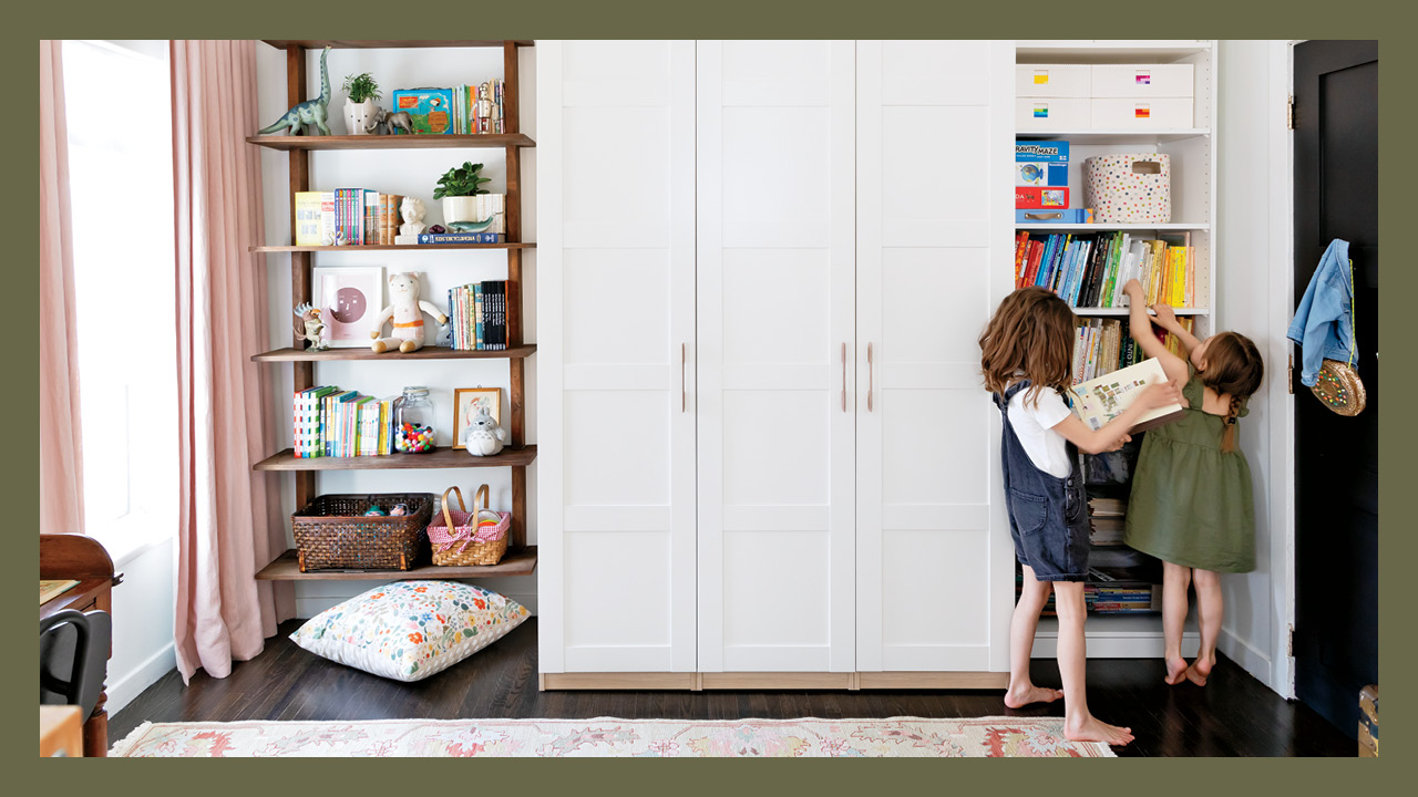 Two little girls standing in front of their wardrobe in their shared room with one door open