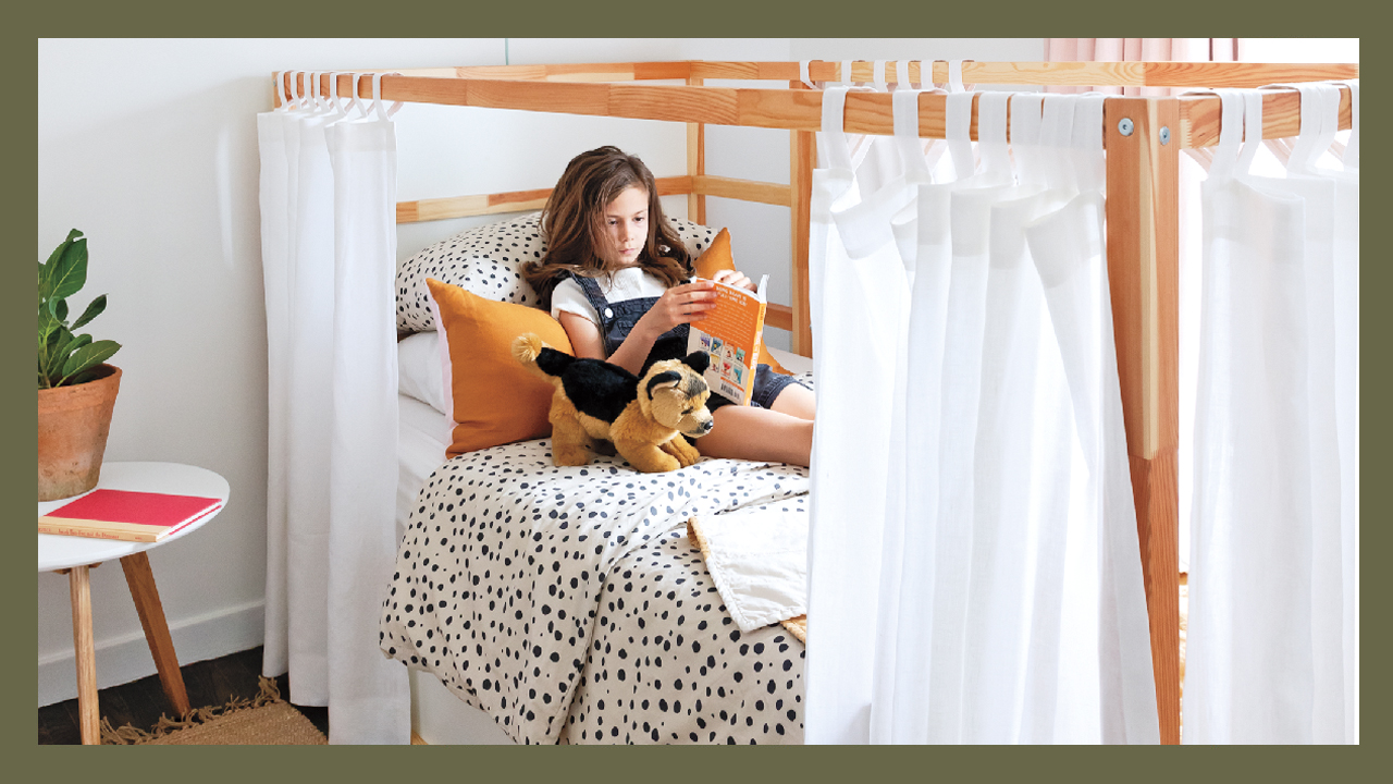 a young girl lies in her bed which has curtains around it