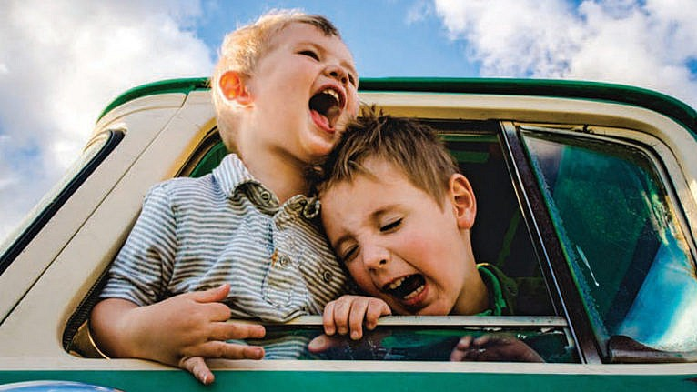 Photo of two kids leaning out of the window of a parked car