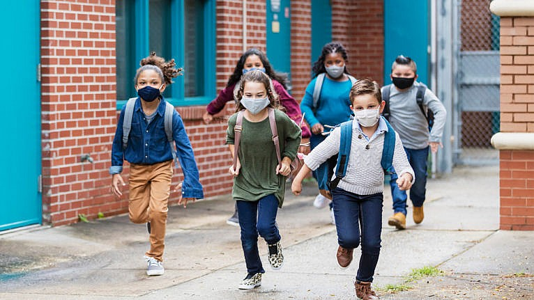 kids in masks leaving school for the day