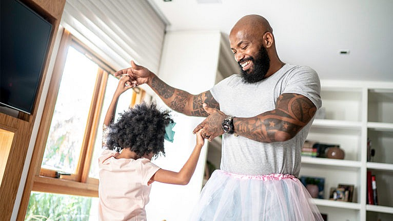 a dad in a tutu dances with his daughter