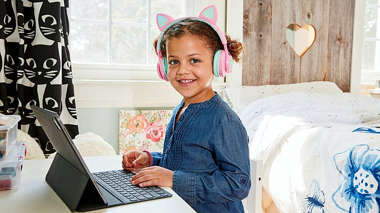 A kid wears animal ear headphones while working on her laptop