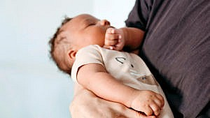 Photo of a newborn sleeping while being held by an adult