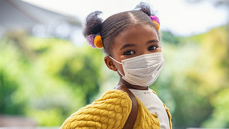 a little girl in a face mask poses for the camera in her backpack