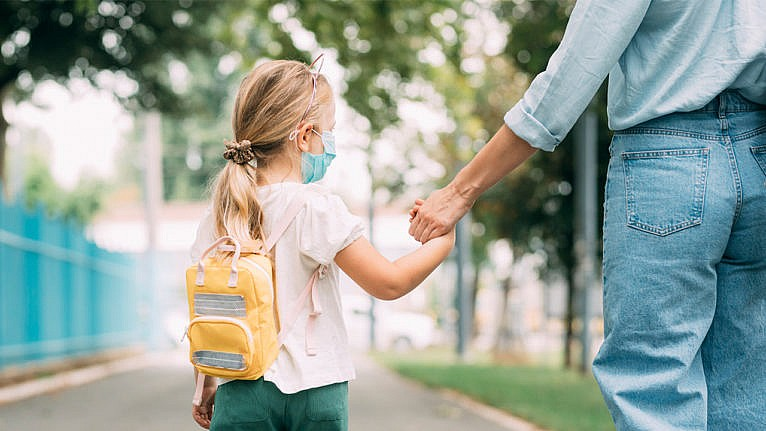 Photo of a kid walking to school wearign a mask and holding their parent's hand