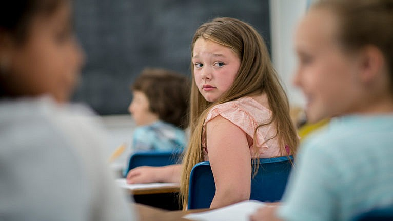 Photo of a girl at school looking back at other kids with a sad expression on her face