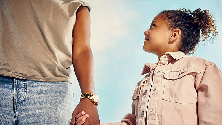 Photo of a kid holding their parent's hand while looking up at them