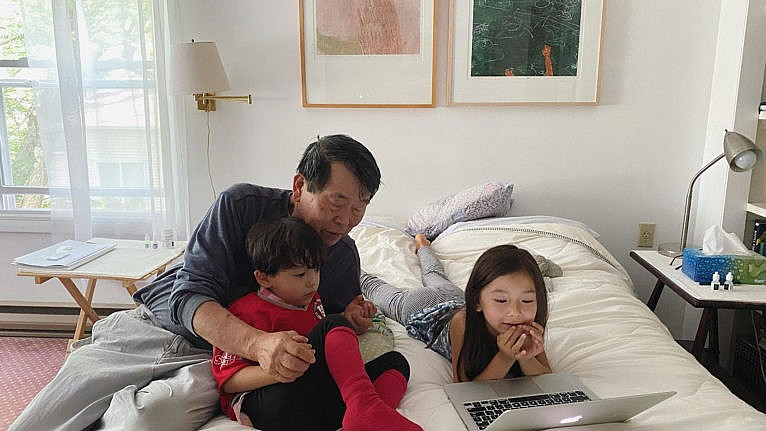 two kids with their grandfather looking at a laptop on a bed