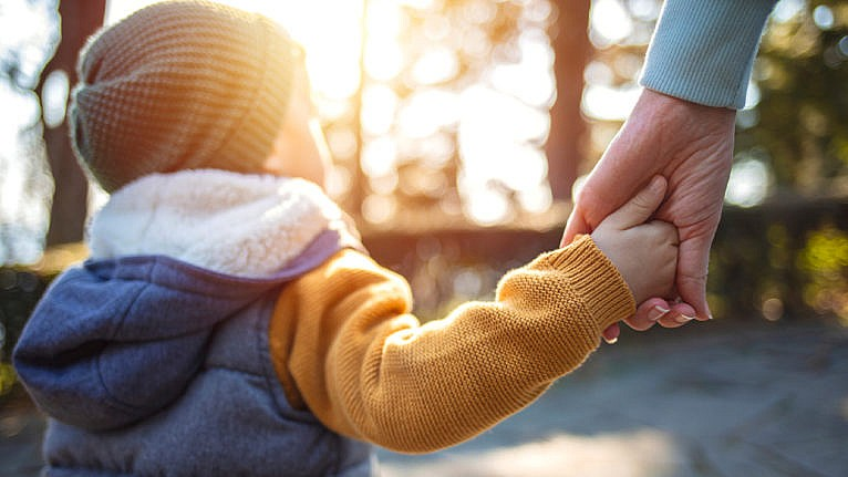 Photo of a kid dressed in fall clothes holding an adults hand while walking outside
