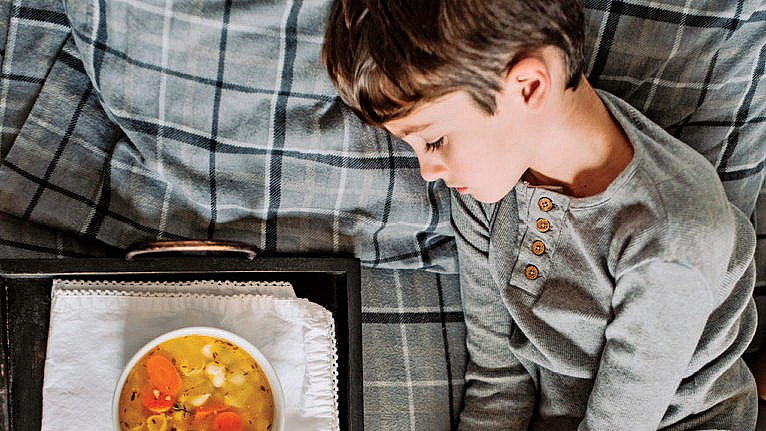 a young boy lies in bed looking sick with a bowl of chicken soup on a tray beside him