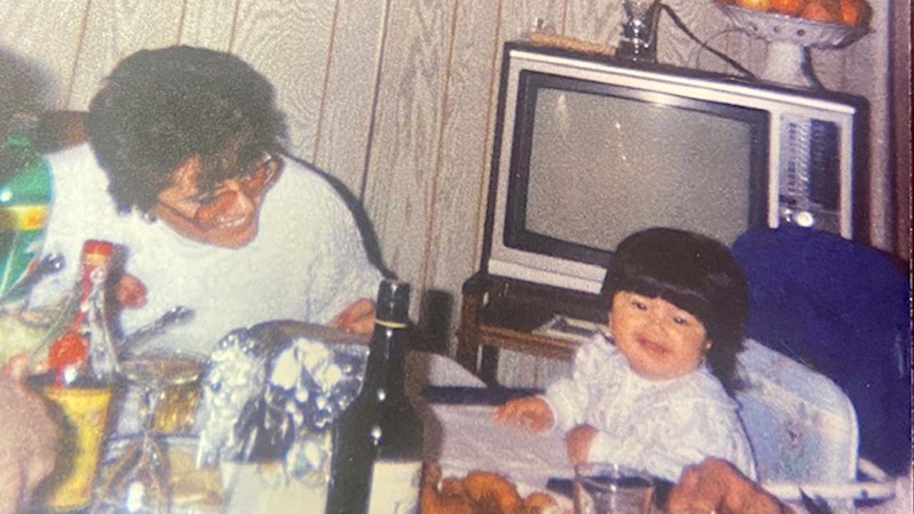 Photo of Melissa sitting in a baby seat on the right and her mother smiling at her on the left. They are sitting at a table with a television in the background.