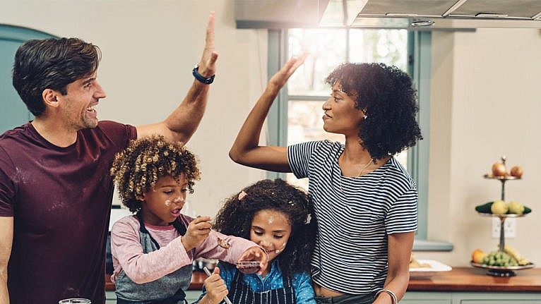 a mom and dad high five while baking with their kids for a story on parenting milestones we don't celebrate but should