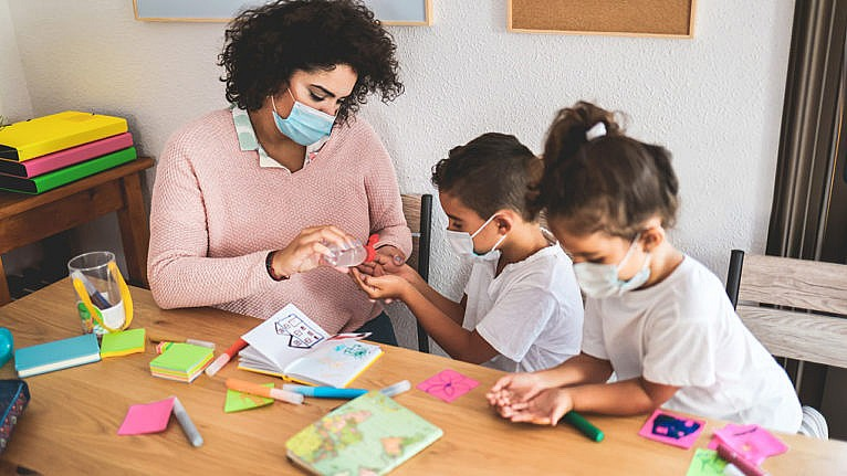 a masked teacher squeezes sanitizer in the hands of two masked children at daycare for a story on the child care platforms of each party in the 2021 Canadian federal election