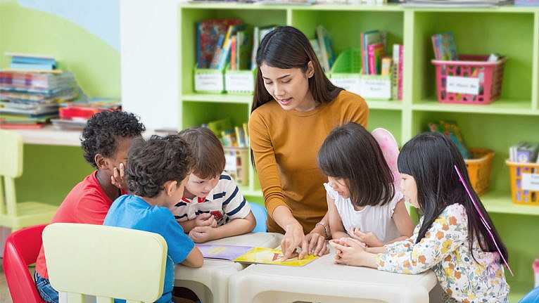 Photo of a teacher pointing to a page of a book while young student gather around the table