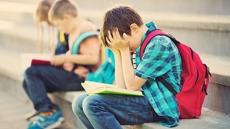 Young boy holds his head in this hands with an open book in his lap