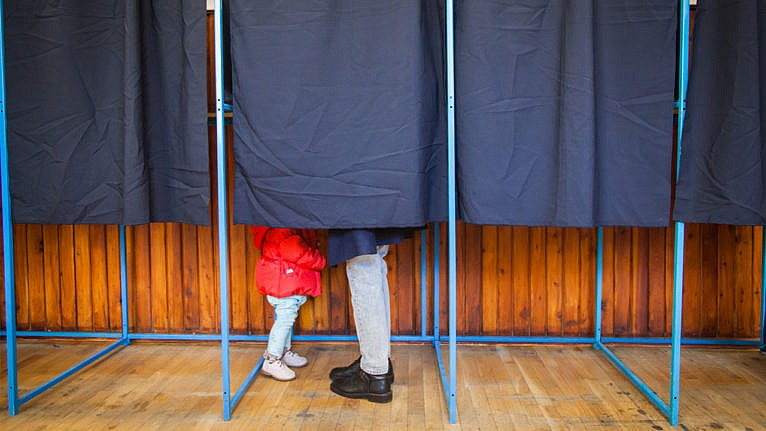 a parent and young child behind the curtain in a voting booth