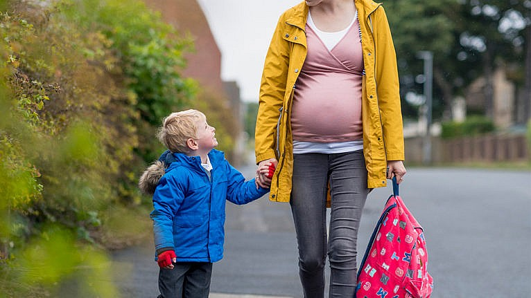Pregnant parent walking their kid to school holding hands