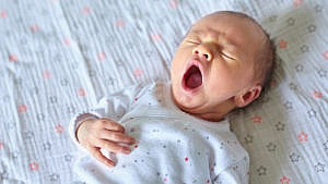 baby yawning with their eye closed