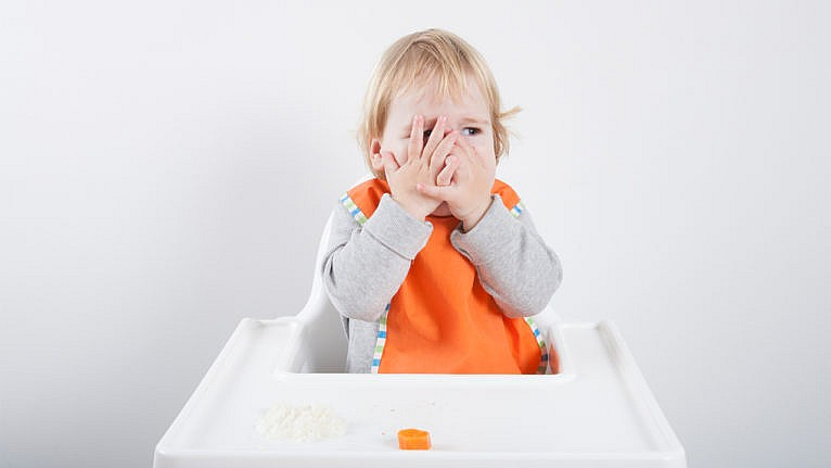 a toddler sits in a high chair with their hands over their face blocking food