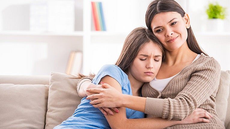 Photo of a mom hugging their daughter while sitting on the couch