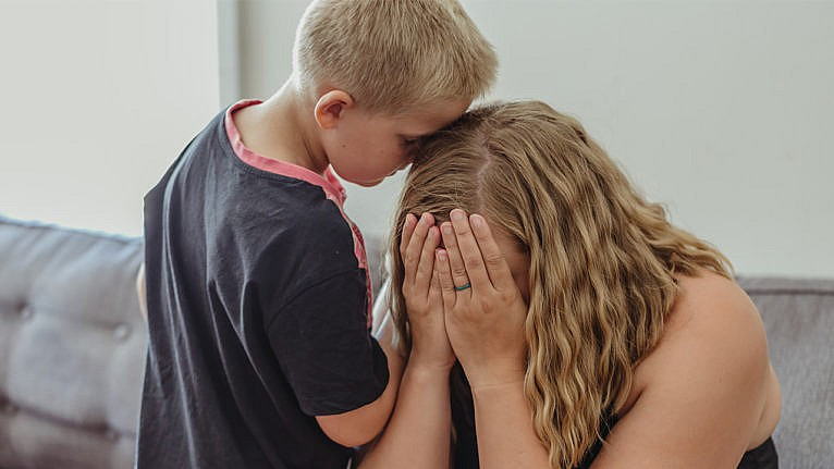 a woman holds her face in her hands while her son stands next to her