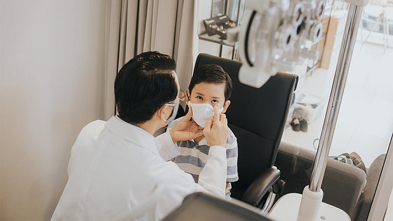 An eye doctor holds a child's face while examining his eyes