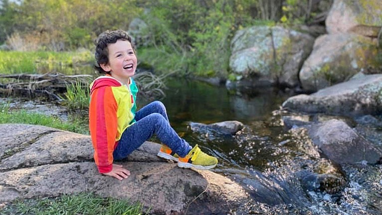 A young boy smiling for the camera sitting beside a waterfall