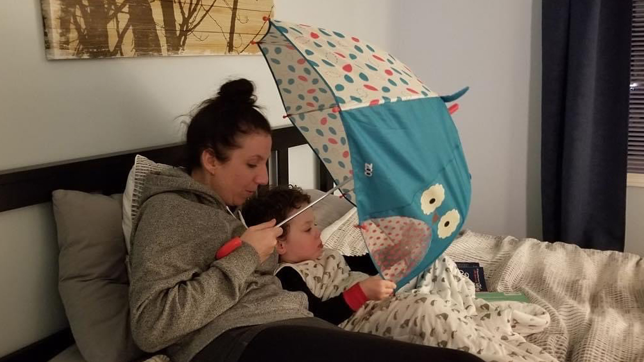A mom and her toddler in bed with an umbrella over them