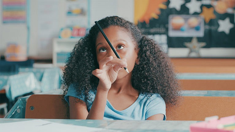a little girl looks at her pencil while trying to focus in class