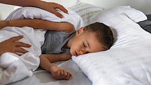 Photo of a little kid lying in bed while a parent checks on them